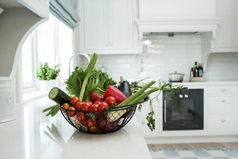 En kurv med grønnsaker blir en frodig fargeklatt mot det ellers stilrene interiøret