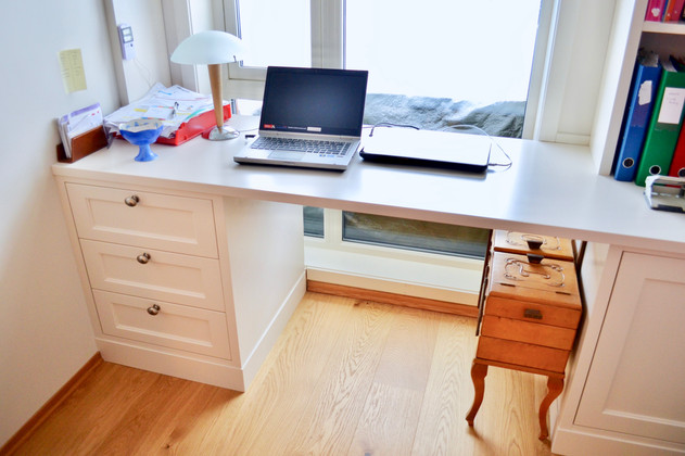 Vegg til vegg tilpasset skrivepult med skap og skuffer på gjesterom eller hjemmekontor. Tilpasset tak, vegger og vindu.  Malt i lys grå farge