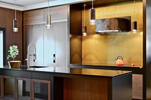 Et moderne plasstilpasset design kjøkken med rene linjer og slette overflater i beiset og lakkert eik, samt malte sorte detaljer