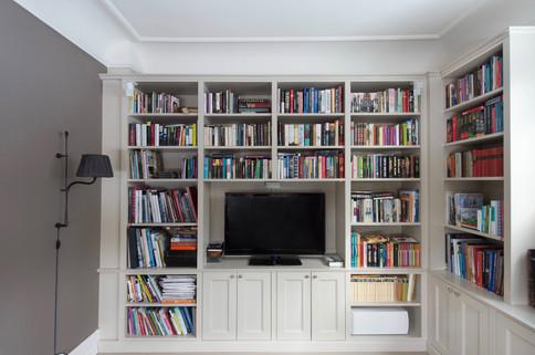 Denne bokhyllen med tv skap er bygget for å få plass til mange bøker og laget med gesims for å ivareta eksisterende taklister i denne tv stuen