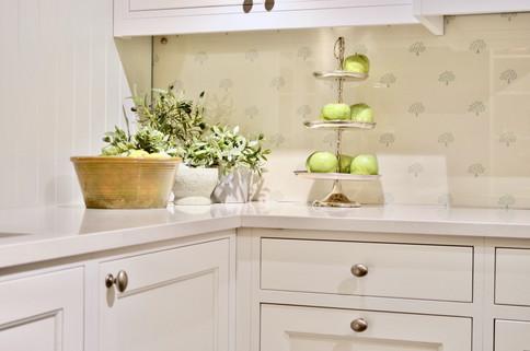 Hvite overflater gir et rent uttrykk balansert med klassiske profiler og knotter i tinn på dette håndverks kjøkkenet