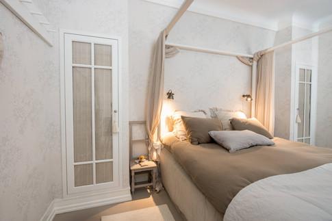 Plassbygde garderobeskap med glassdører med innvendige gardiner. Malt i lys grå kombinert med jordfargede tekstiler