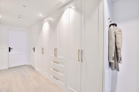 Entré garderobe i klassisk hvit med lange håndtak og knagger i antikk messing