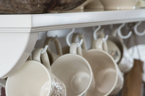 Åpne hyller med kjøkkenutstyr bryter med de ellers slette overflatene