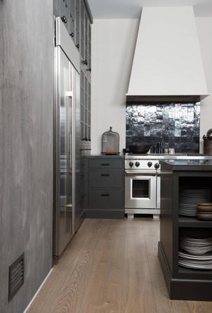 Betong og stål mot grått og sort skaper et maskulint uttrykk på dette kjøkkenet