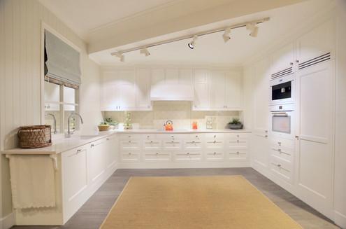 Hvitt tema preger denne kjøkkeninnredningen som ellers har en balansert blanding av slette og profilerte, innfelte fronter. En håndlaget kjøkkenhette i senter