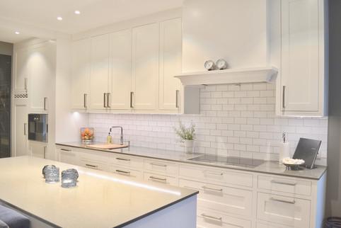 Godt med benk og skapplass i et stilrent design. Profilene på kjøkkenhetta gir et friskt stilbrudd. Mørk grå kompositt benkeplater