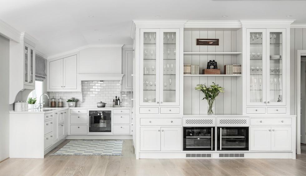 Spesial designet kjøkken med innfelte fronter i fired earth earl grey farge. Skap og kjøkkenhette tilpasset skråtak. Seksjon med glasskap til benk med integrerte vinskap