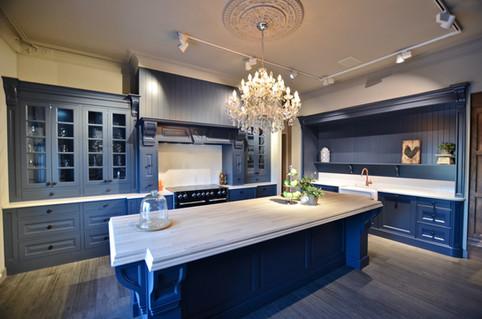 Eksklusivt herregård kjøkken i klassisk stil med stor kjøkkenøy og grue. Vitrineskap med glassdører og kraftig utsmykket gesims. Malt i Deco Blue farge