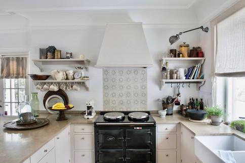 Håndverks kjøkken i landlig stil med innfelte fronter og frittstående kjøkkenhette med historiske fliser og åpne hyller med hylleknekter
