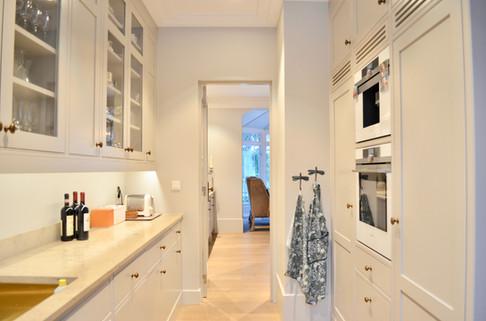 Romslig grovkjøkken med inngang mot hovedkjøkkenet. Hvitevarer fra Siemens