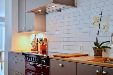 I hjertet av kjøkkenet finner vi kokeområdet med den røde falcon komfyren med romslig plass opp til en stilren spesiallaget kjøkkenhette