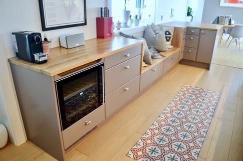 Spesialtilpasset kjøkkeninnredning med massiv eik benkeplater og skreddersydd sittebenk med håndsydde puter. Vinskap fra Norcool. Malte slette fronter i lys grå farge