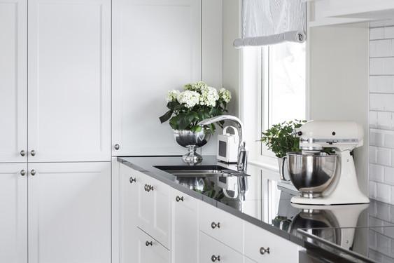 Kjøkkeninnredning med en kombinasjon av slette og profilerte fronter i lys farge. underlimt vask i mørk granitt benkeplate