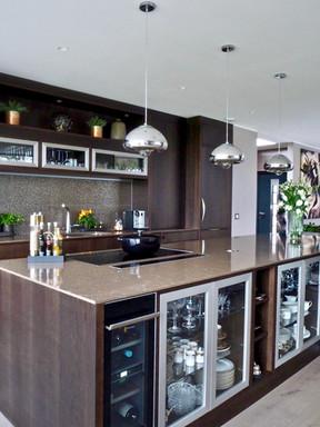 Vinskap integrert i kjøkkenøya. Sort mot brunt og aluminium gir et moderne preg