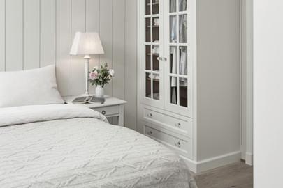 Klassisk designet garderobeskap på soverom med glassdører i lys grå farge som harmonerer med tekstilene