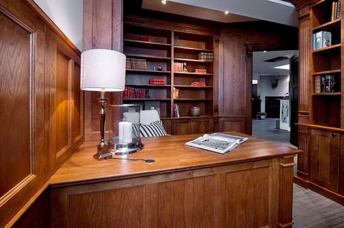 Eksklusiv bibliotek innredning i mørkbeiset eik med skrivepult, bokhyller spesialtilpasset mot brystninger i samme old english style
