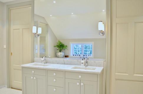 Baderomsinnredning med plasstilpasset speil og lamper på hver side