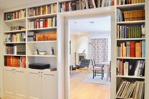 Vegg til vegg tilpasset bokhylle i bibliotek. Lys grå farge