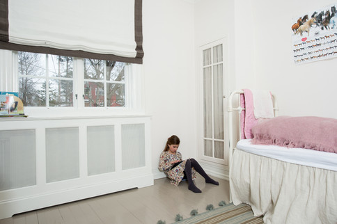 Innredning på barnerommet med innebyggede garderobeskap med glassdører - Radiatorskjuler med hylle på topp og matchende tekstiler i lys duse farger