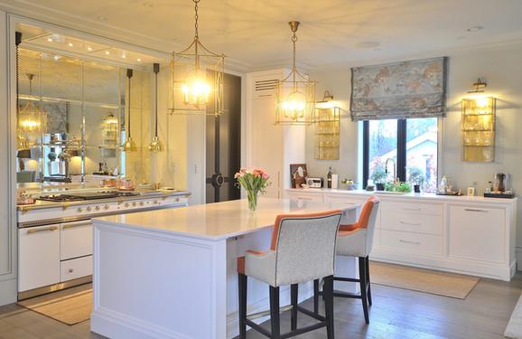 Et unikt og elegant kjøkken i klassisk hvit, speilglass og polert messing. Utsøkt design av Gustavian AS og Gjennomtenkte løsninger laget av Bokhyllespesialisten