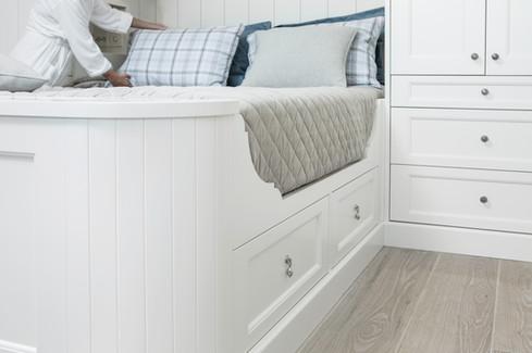 Interiørdetaljer fra seng med praktiske skuffer til dyner og puter