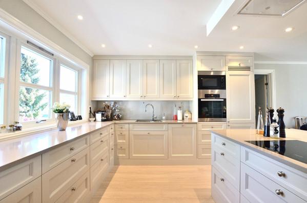 Godt med lagringsplass under benk med overskap og høyskap samlet på samme vegg skaper et åpent kjøkkenlandskap