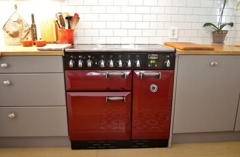 Den røde Falcon Elan komfyren i kirsebær farge kommer til sin rett mot den lys grå kjøkkeninnredningen