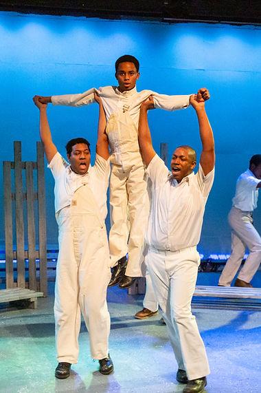 Two men lifing one boy, Scottsboro Boys - Vintage Theatre