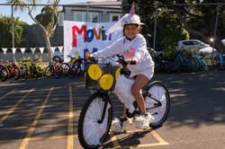 IBS girl on white bike and banner