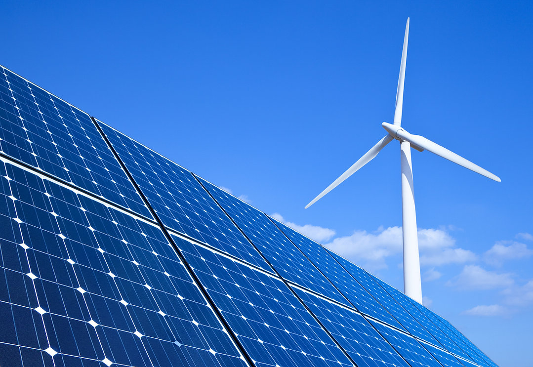 Solar panels and wind turbine against bl