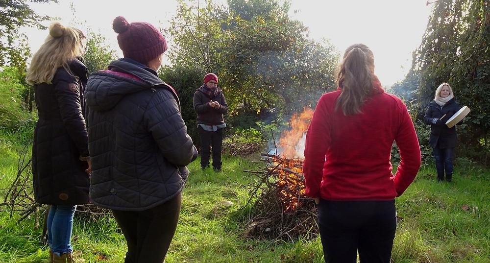 Frauen stehen um ein Lagerfeuer, es wird getrommelt