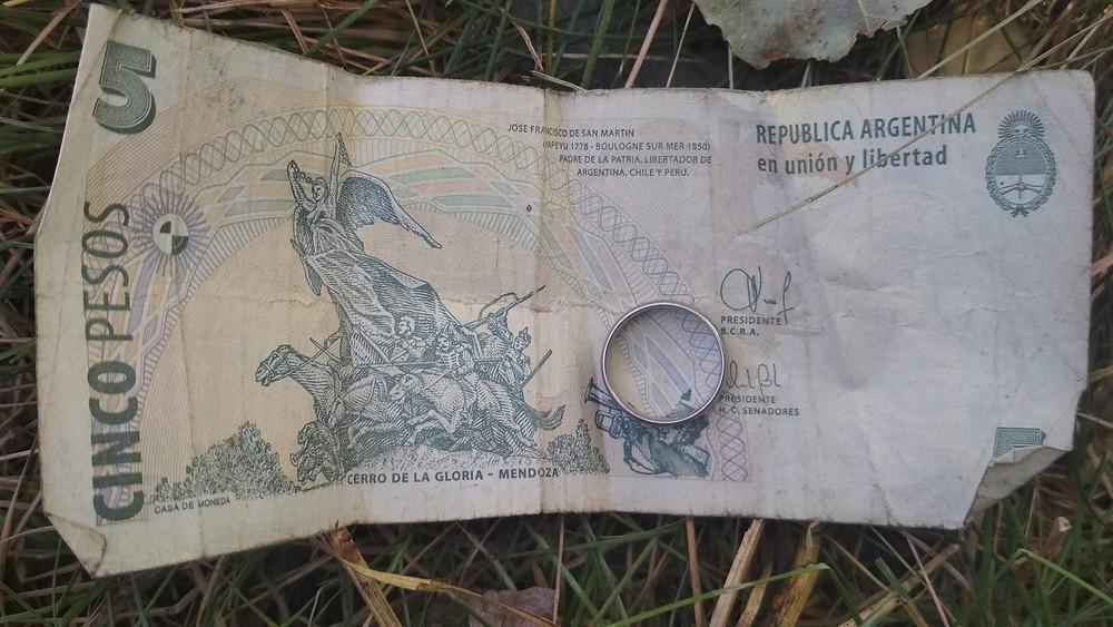 ein Ring liegt auf einem argentinischen Fünf-Peso-Schein