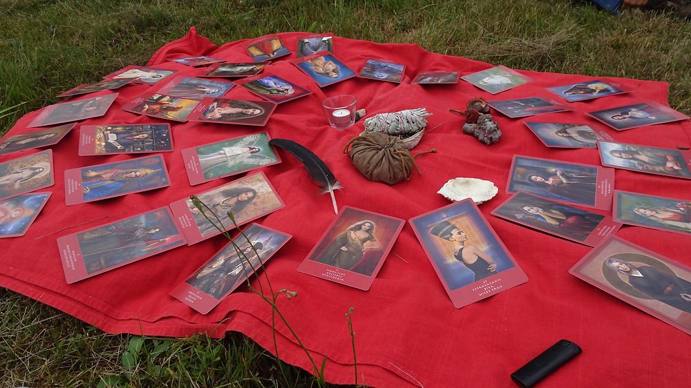 Karten mit Archetypen liegen auf einem roten Tuch, Feder, Salbeibündel, Abalone