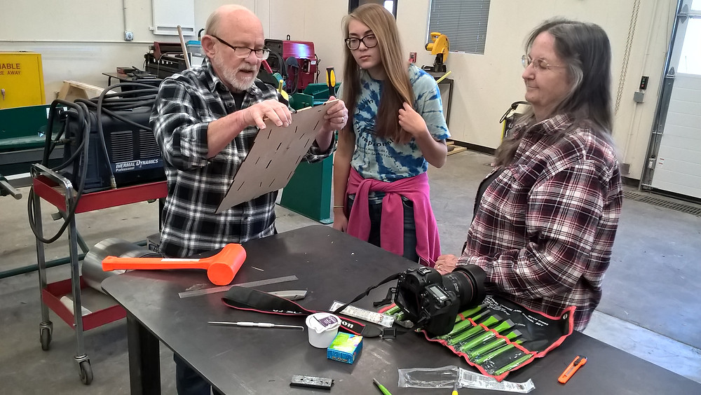 Jenae Morris (center) observing how to put together the pieces she designed for an upcoming gumball project helped by mentors Dave (left) and Bert (right)