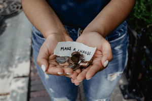 Hands holding money and a note saying make a change to encourage donations to a mental health cause