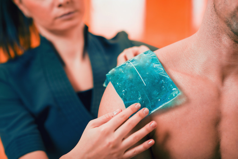 A medical professional applying an ice pack to a patient's shoulder.