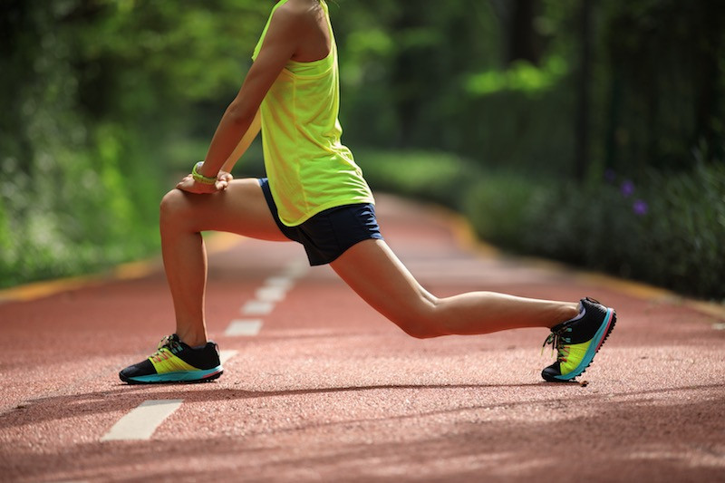 A Woman doing leg stretches on a running track.