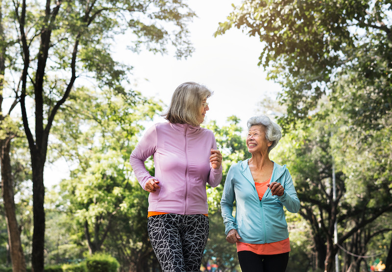 Two elderly women in athletic clothing talking a walk in a wooded area.