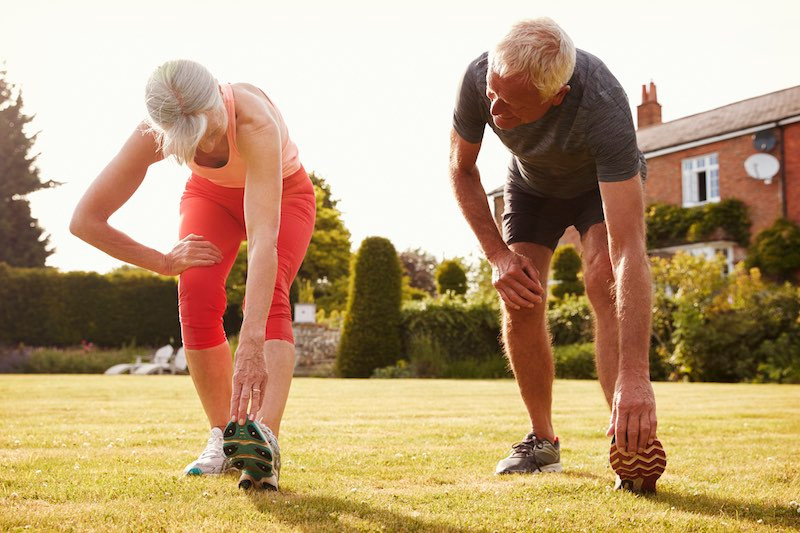 Older couple doing leg stretches before going for a walk.