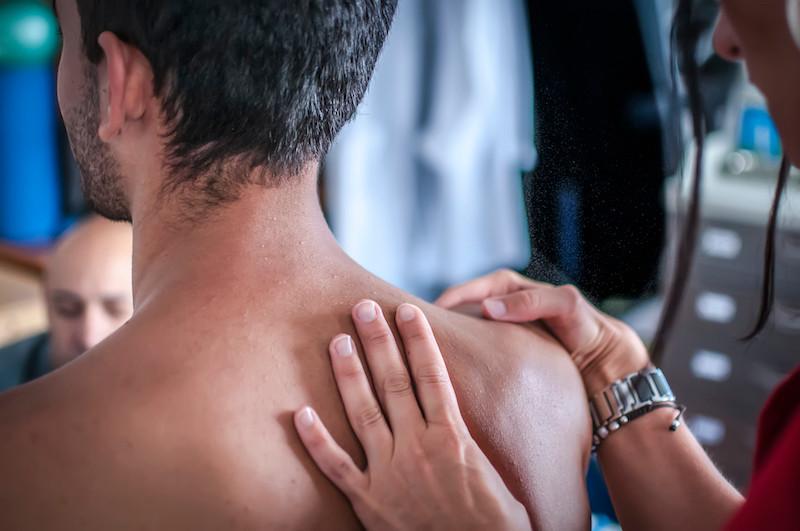 A medical professional helping a patient preform shoulder stretches.