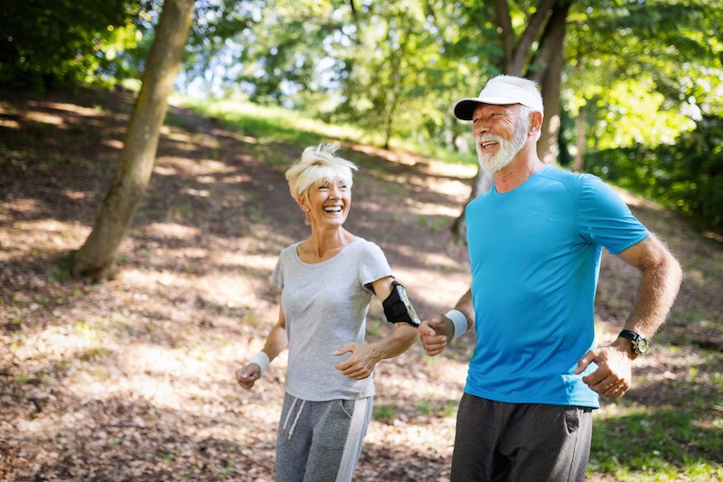 An older male and female in athletic wear going for a walk together in a scenic area.