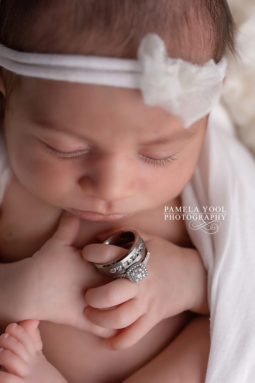 Newborn with parents wedding rings