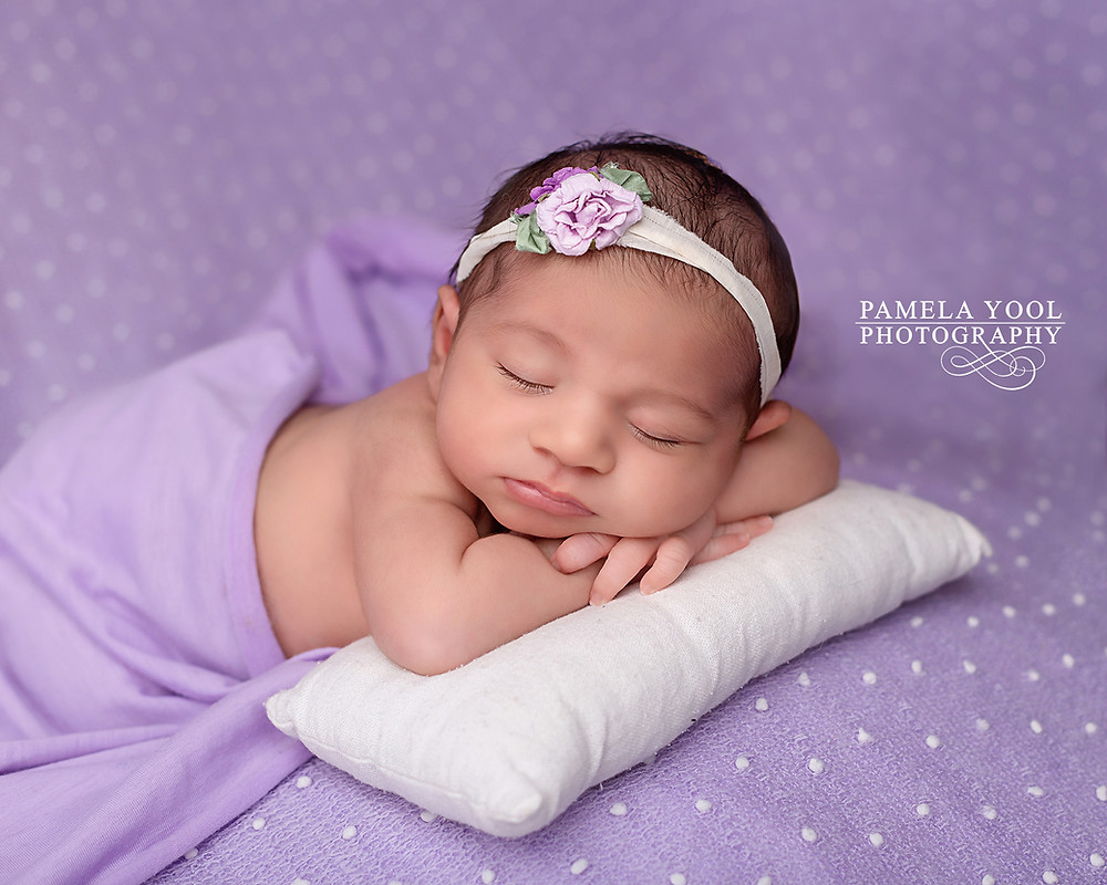Newborn sleeping with floral lavender hand band