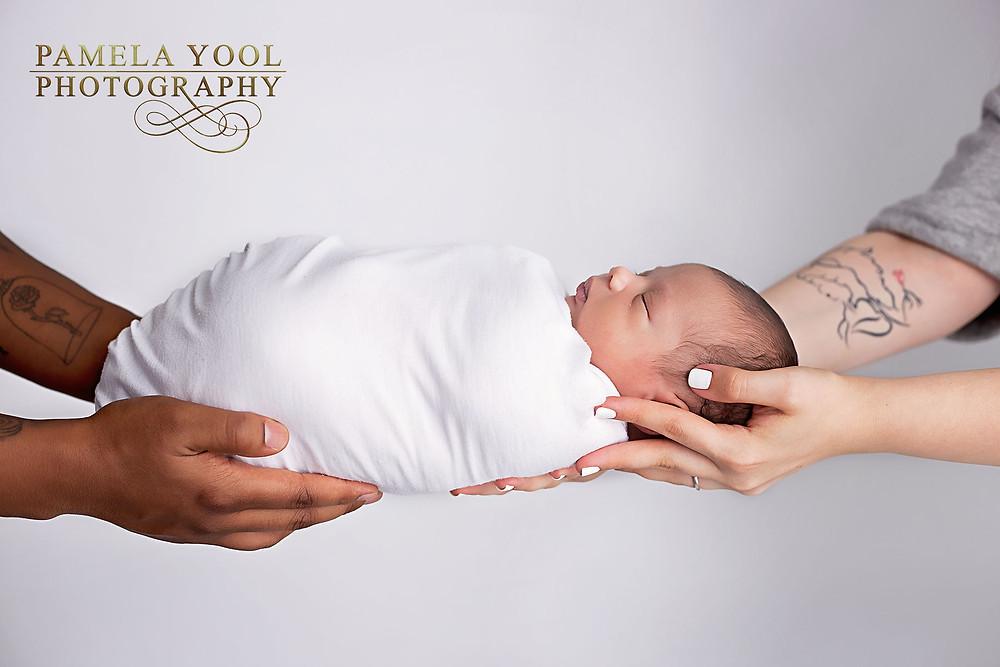 Newborn in Parents hands Portrait