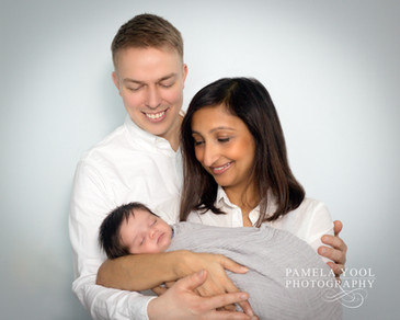 Newborn Lifestyle Photo of parents holding sleeping baby boy