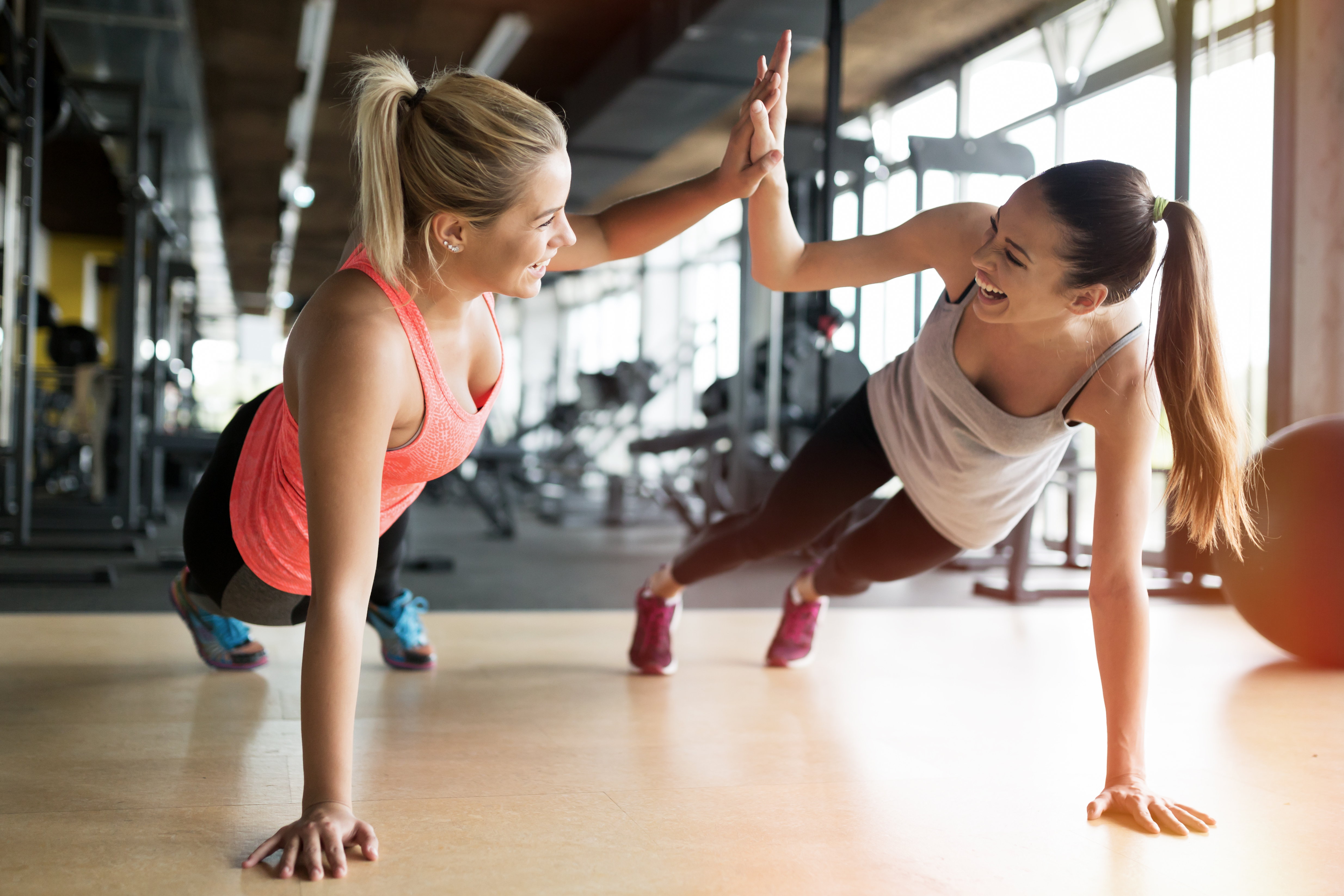 Beautiful women working out in gym toget