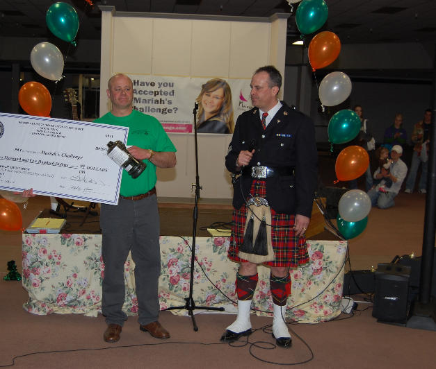 Terry Rocchio presenting a cheque to Maria's father, Leo McCarthy, for $2500 from the Pipes and Drums of the Edmonton Police Service