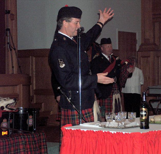Retired S/Sgt. Kevin Quail addresses the haggis