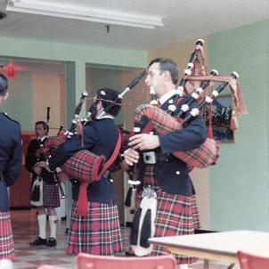 P/M D. Scott tuning the Band in barracks, Inuvik, NWT, July 1983. Backs to camera, left, Dick Ellsworth, middle, Murdock Jardine, right, P/Sgt. Peter Demers. Facing camera, left, Wayne Anderson, right, Blake MacEachern